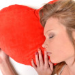 Attractive young woman hugging heart-shaped pillow. All on white background — Stock Photo #8928734