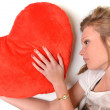 Attractive young woman hugging heart-shaped pillow. All on white background — Stock Photo #8928743