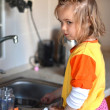 Little baby washing the dishes in the kitchen - Stock fotografie