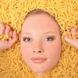 Portrait of a young beautiful woman in pasta — Stock Photo