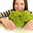 Happy young woman holding green lettuce and smiling, over white background — Stock Photo