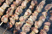 Tasty grilled meat on skewers — Stock Photo