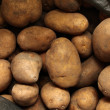 Overflowing bag of potatos — Stock Photo