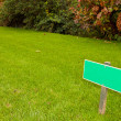 Green grass with a sign and a bush, sideview horizontal shot — Stock Photo