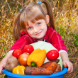 Little girl with fresh vegetables in garden — Stock Photo