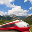 Fast train passing by mountain landscape - Stock Photo