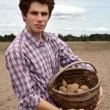 Stock Photo: Young agriculturist showing his crops