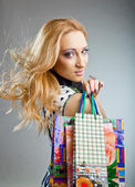 Smiling beautiful woman with paper shopping bags — Stock Photo