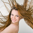 Cheerful young woman with developing hair — Stock Photo