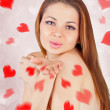 Beautiful woman blowing kisses with red palm — Stock Photo #8512713