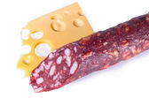 Piece Swiss cheese with holes a stick of smoked sausage with fat — Stock Photo