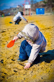 Little boy digs in sand — Stock Photo