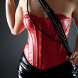 Stock Photo: Womin red leather corset with black whip