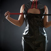 Woman in red leather corset with whip — Stock Photo