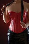 Woman in red leather corset with black whip — Stock Photo