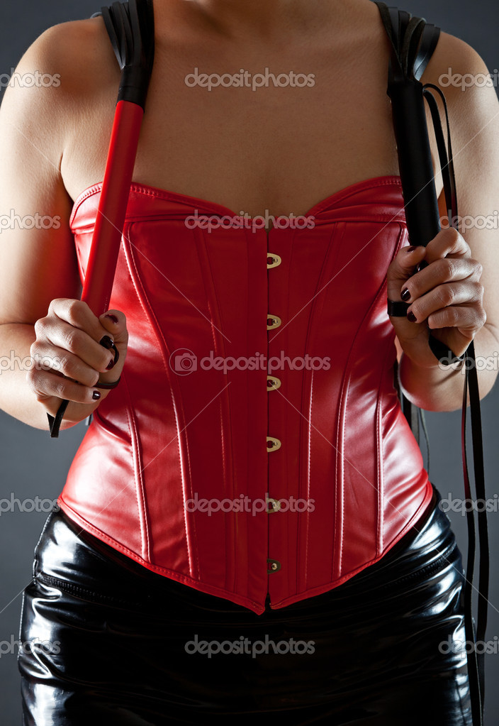 Sexy woman in red leather corset with  whips  Stock Photo #9284223