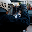 Police Officer Films Protesters - Stock Photo
