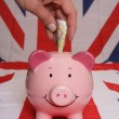 Stock Photo: Saving ten pounds with piggybank