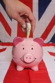 Saving ten pounds with piggybank — Stock Photo