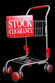 Shopping trolley with stock clearance sign — Stock Photo