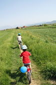 Children riding a bicycle along the banks — Stock Photo