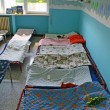 Stock Photo: Dormitory for children with small beds and blankets for kindergarten