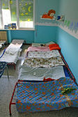 Dormitory for children with small beds and blankets for a kindergarten — Stock Photo