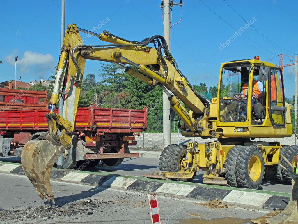 Roadworks with a yellow scraper to work in the middle of the road — Stock Photo #10475064