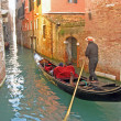 Gondolier in gondolalong canal — Stock Photo #10560834