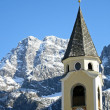 Bell Tower of a church and the background of the Dolomites — Stock Photo