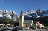 Bell Tower of a church and the background of the Dolomites in Ca — Stock Photo