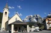 Bell Tower of a church and the background of the Dolomites in It — Stock Photo