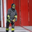 Stock Photo: Firemwhile unrolls fire hose to extinguish flames
