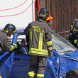Постер, плакат: Firefighters in action for free from a car injured in a car acc