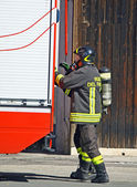 Firefighter with oxygen cylinder and open the fire trucks — Foto Stock