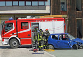 Car destroyed in a traffic accident and firefighter — Stock Photo