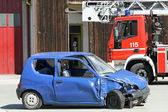 Car destroyed in a traffic accident and trucks of firefighter — Stock Photo