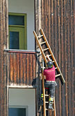 Fireman while mounting a ladder to climb up a building — Stock Photo