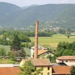 Large brick smokestack of a furnace and the hills — Stock Photo