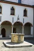Kreuzgang des klosters mit dem alten brunnen — Stockfoto