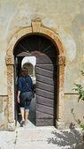 Eski bir manastırda bir kapı giren kadın — Stok fotoğraf