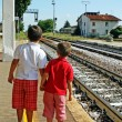 Two brothers, children waiting for the train station — Stock Photo