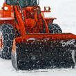 Orange snow plow clears the streets during a snow storm - Stock Photo