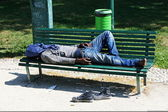 Poor marginalized homeless sleeping in a outdoor bench — Stock Photo