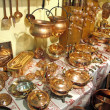 Pots and pans gleaming copper for sale at the market - Stock Photo