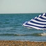 Striped umbrella on the beach and sea — Stock Photo