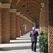 Stock Photo: Priest walking along arcades of cemetery