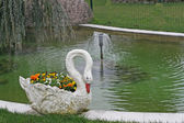 Vase in the shape of swans on the shore of a pond — Stock Photo