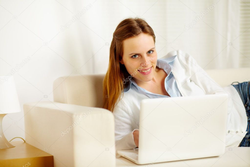 Portrait of a attractive caucasian woman lying on sofa with a laptop and looking at you — Stock Photo #10218895