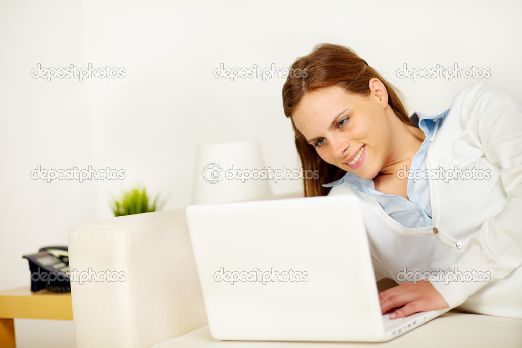 Portrait of a cheerful young woman lying on sofa and working on laptop  Stock Photo #10218905